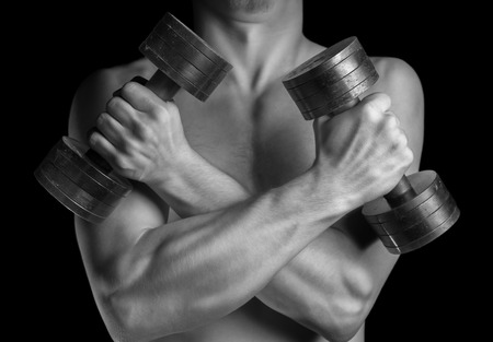 Muscular man holds dumbbells with arms crossed, monochrome image photo