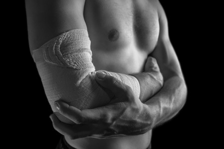 Man holds his elbow joint, acute pain in the elbow, monochrome image photo