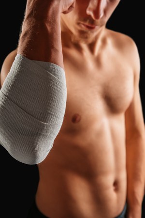 Man with bandaged elbow joint, tension photo
