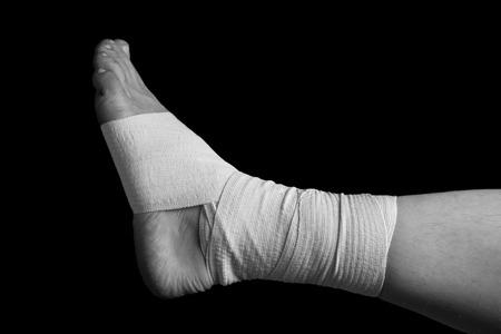 bandaged: Bandaged leg, foot sprain, monochrome image Stock Photo