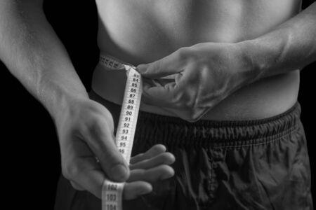 unrecognizable: Unrecognizable man is measuring waist, monochrome image