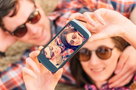 Happy hipster couple takes photographs self portrait with camera phone