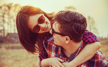 serene people: Young happy woman in glasses embraces a man, scene at sunset