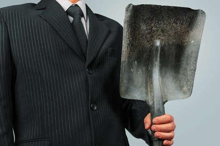 power shovel: Unrecognizable businessman holds metal shovel, concept of business creation