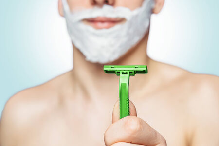 Man with foam on his face holds green razor photo