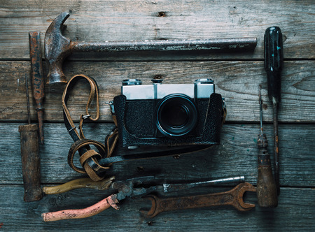 Set of old working tools and retro photo camera on wooden table, top view photo