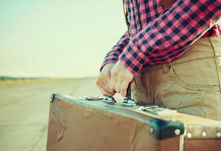 unrecognizable: Unrecognizable woman holds vintage suitcase, close-up