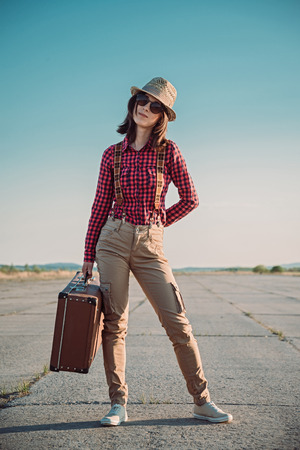 Young hipster woman holds vintage suitcase on the roa photo