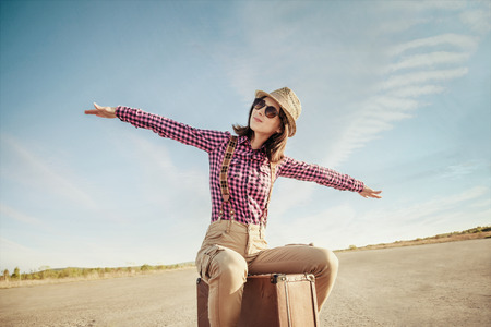 Happy hipster girl sits on vintage suitcase on road and makes a gesture of flight