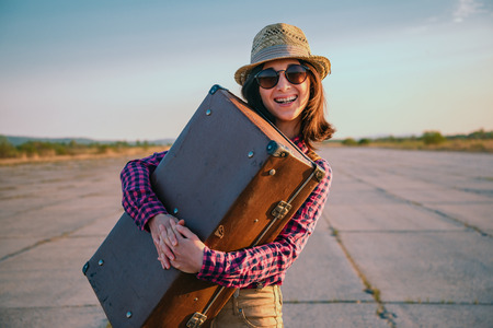 Happy woman traveler embraces a vintage suitcase on road photo