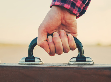 road travel: Close-up image of female hand with suitcase handle
