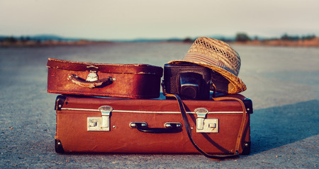 Vintage suitcases, photo camera and hat on road, concept of travel Foto de archivo