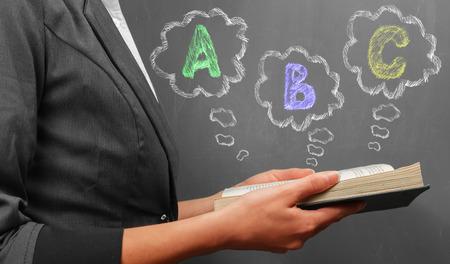 unrecognizable: Teacher woman in suit reads a book near a blackboard, ABC alphabet