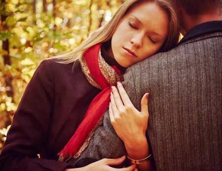 hugging couple: Young beautiful woman with closed eyes embraces a man in autumn park