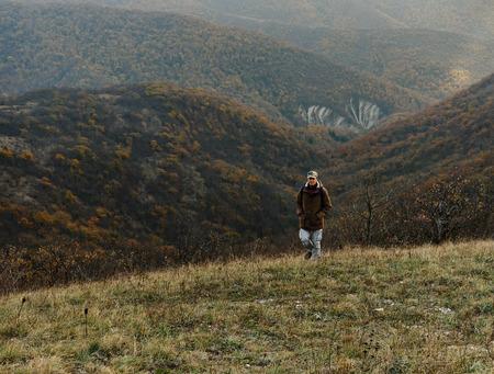Hiker man climbing the mountain at autumn season photo
