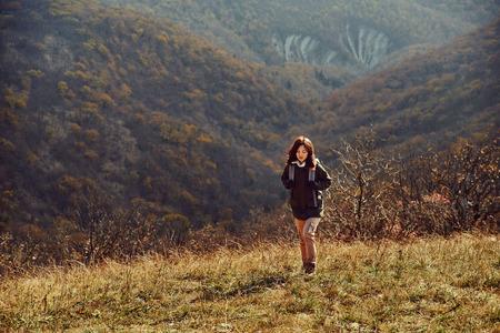 Hiker woman walking among the mountains at autumn season photo