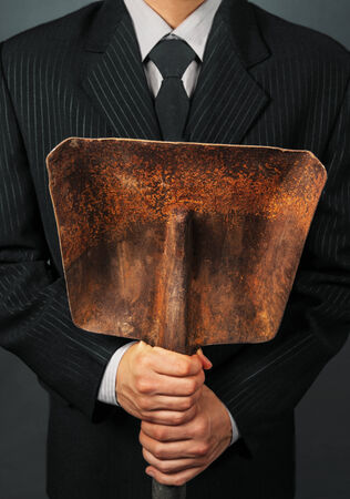 power shovel: Businessman in a suit holding metal shovel, face is not visible. Concept of business creation Stock Photo