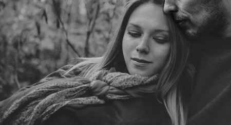 black man white woman: Smiling couple in love rests in park, man embraces a woman. Black and white image