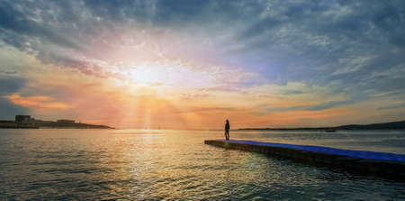 Woman standing on pier near the sea and looking at sunset, tranquil scene. Beautiful seascape. Image with sunlight effect