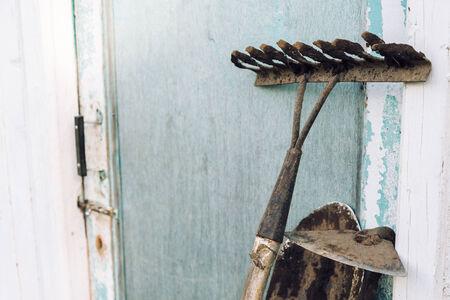 hoe: Gardening tools: hoe, shovel and rake near a shed