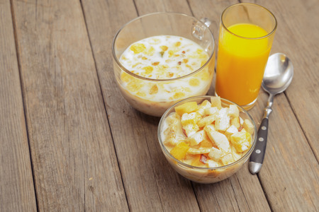 Oatmeal with milk and fruit salad for breakfast on a wooden table, space for text photo