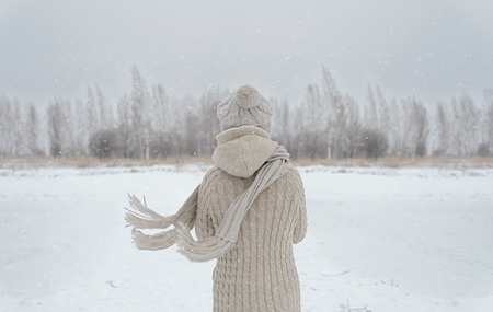Unrecognizable woman stands back in the woods in winter Stock Photo