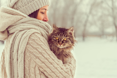 Young woman holds a cat outdoors in winter weather