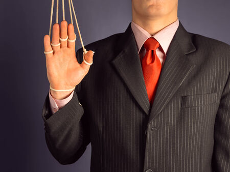 marionette: Marionette businessman makes a welcome gesture, hand on the ropes Stock Photo