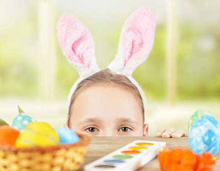 face paint: Little girl dressed in bunny ears looks out the table with decorations for Easter Stock Photo