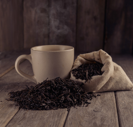 raw tea: Cup of black tea next to a black leaf tea on a wooden table