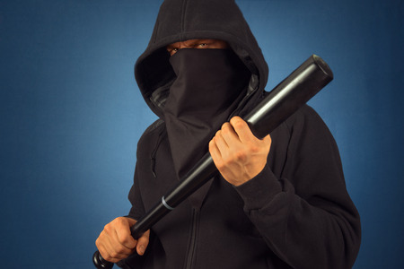 Dangerous man in the mask with baseball bat ready for fight