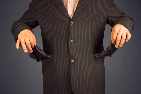 Man in a suit with pockets turned inside out. concept of crisis