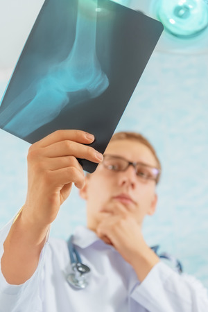 operate: Man doctor looks at x-ray image of knee joint in a hospital