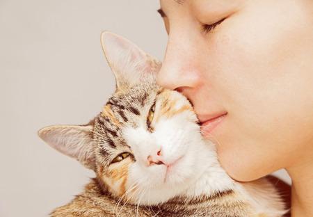 feline: Happy woman is hugging orange tabby feline Stock Photo