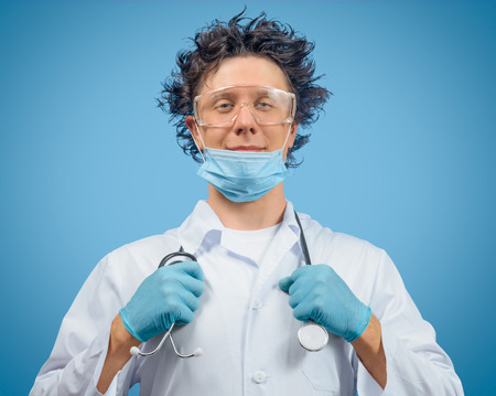 mad scientist: Crazy man doctor is holding stethoscope on a blue background