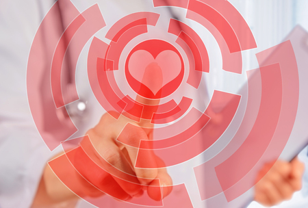 Unrecognizable woman doctor is touching shape of red heart, concept of healthcare photo
