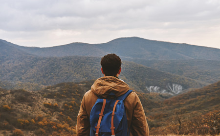Hiker man with backpack enjoying landscape of autumn mountains, rear view