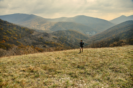 Hiker young woman with backpack walking in autumn mountains. Landscape of mountains