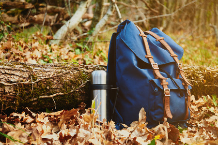 Thermos and backpack outdoors on autumn nature, hiking theme