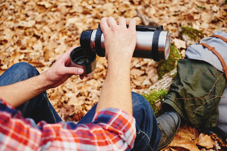 thermos: Unrecognizable hiker man pours tea or coffee  from thermos in autumn forest. Hiking and leisure theme Stock Photo
