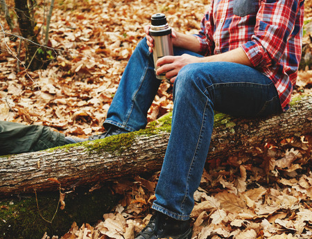 thermos: Unrecognizable hiker man holding a cup of  tea or coffee and  thermos and sitting on tree trunk in autumn forest. Hiking and leisure theme Stock Photo