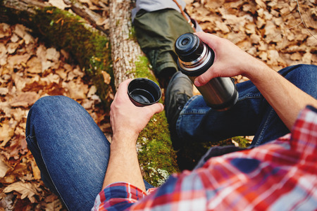 Unrecognizable hiker man holding a cup of  tea or coffee and  thermos in autumn forest. Hiking and leisure theme Standard-Bild