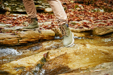 crossing legs: Hiker woman crossing a stream in autumn forest, view of legs. Hiking and leisure theme