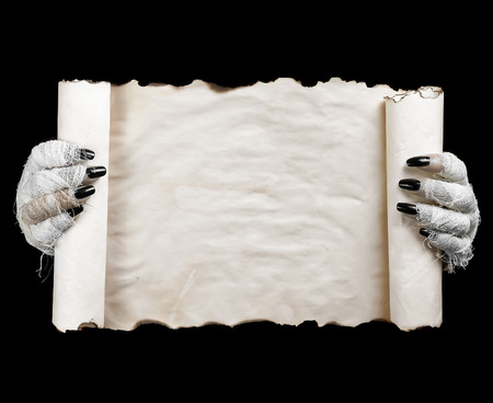 halloween concept: Hands of mummy holding horizontal scroll on dark  background. Space for text.