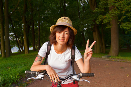 victory sign: Hipster girl doing victory sign while sitting on a bicycle