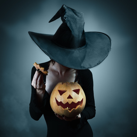 costumes: Woman in witch costume opens carved Halloween pumpkin