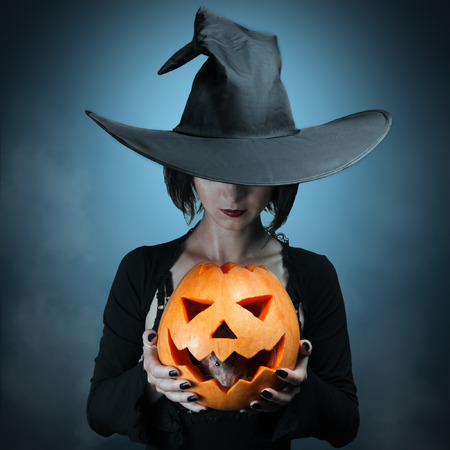 scary witch: Halloween witch holding a orange pumpkin, which sits inside a mouse Stock Photo