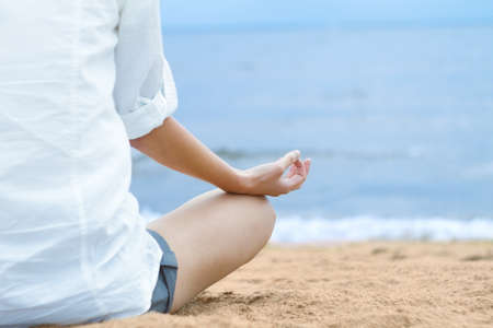 woman posture: Young woman meditating in lotus position while sitting on beach