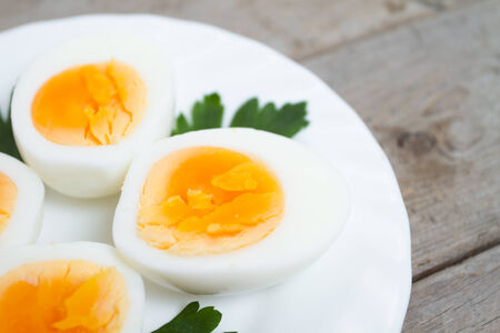 Sliced hard boiled eggs with parsley on a white plate, close-up