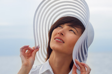 brim: Beautiful young woman in a hat with a wide brim at sea Stock Photo